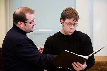Student reviewing music score with professor