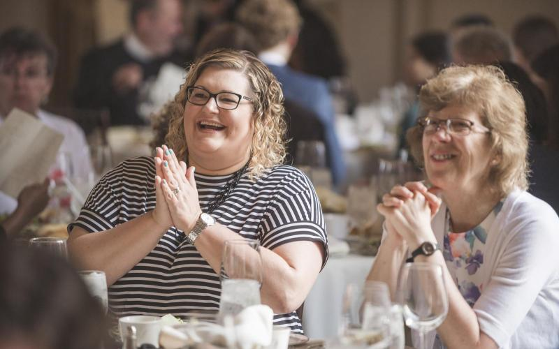 Laura Adam and Laurie Ongley enjoy the banquet slideshow